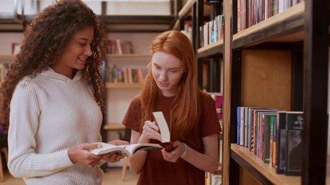 Young beautiful girl with curly hair and white sweater discussing books with female redhead teenage in library smiling