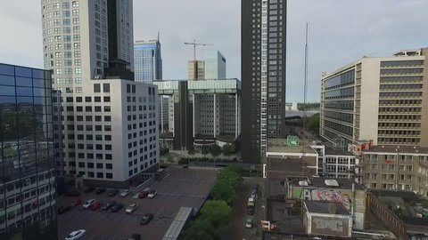 Aerial video in the center of Rotterdam, flying low between skyscrapers towards the new central station.