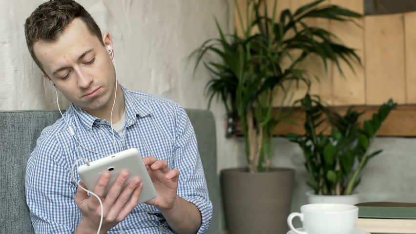 Unhappy man looks thoughtful while listening music in the cafe  | Shutterstock HD Video #24248891