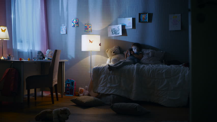 Cute Little Girl Lies on Her Bed and Watches Cartoons on a Smartphone. Her Kitten is Beside Her Playing. Her Floor Lamp is On. Shot on RED EPIC-W 8K Helium Cinema Camera.