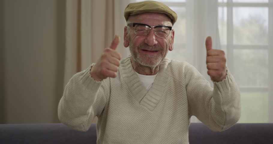 Senior man giving a thumbs up while sitting on a sofa. Shot on RED 4K