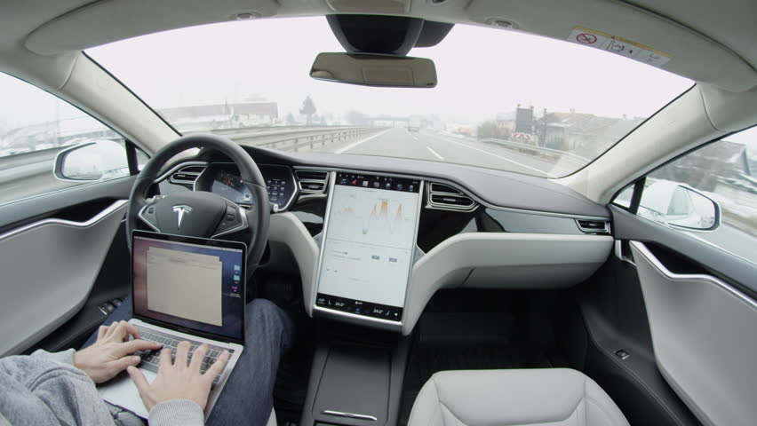 LJUBLJANA, SLOVENIA - FEBRUARY 4, 2017: Luxury Tesla Model S autonomous automated electric car self-driving on freeway in the morning. Unrecognizable businessman working on laptop while traveling