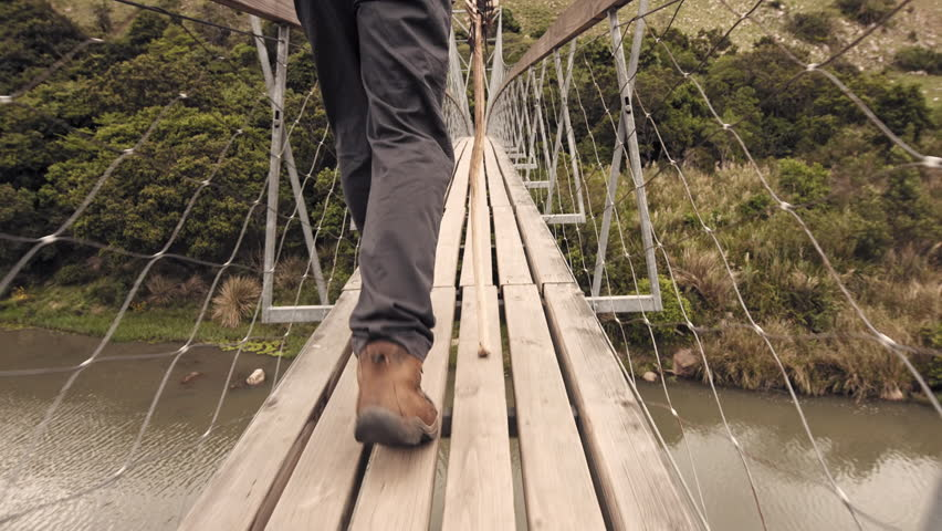 4k close up of hiking boots, trekker walking with walking stick on wood sespention footbridge on walking adventure in mountains.  | Shutterstock HD Video #24258311