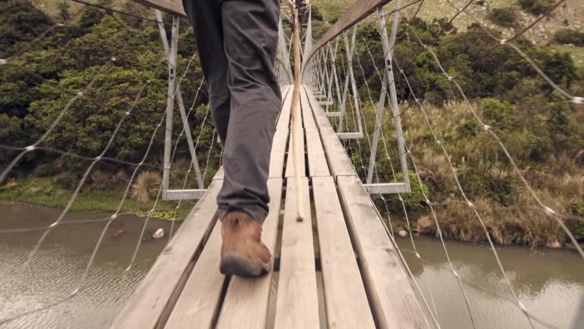 4k close up of hiking boots, trekker walking with walking stick on wood sespention footbridge on walking adventure in mountains.  | Shutterstock HD Video #24258311
