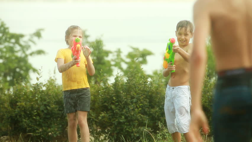 Children fighting playfully with water guns