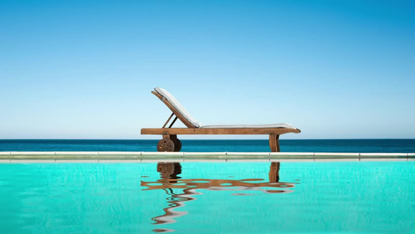 Seamless loop - Reclining chair near a swimming pool, sea and blue sky, water reflections, video HD