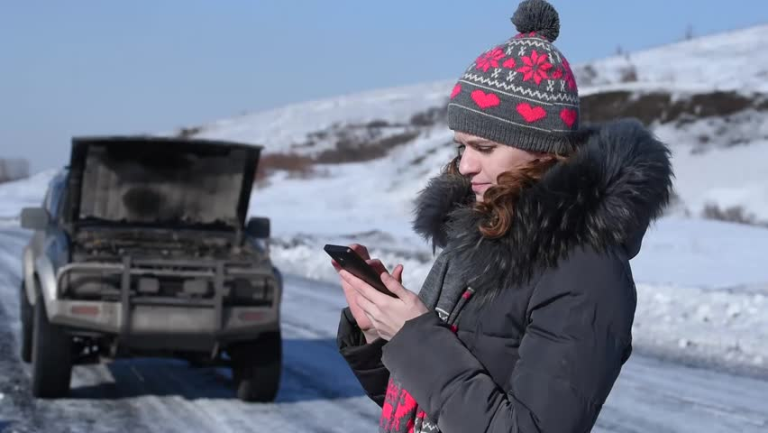 Broken car on a winter road and a woman wants to make a phone call to ask for help, but there is no connection, and she was crying | Shutterstock HD Video #24339701