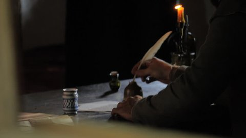 VIRGINIA - JULY 2016 - Reenactment, 16th - 18th Century era recreation -- Writing with a quill at candle light
