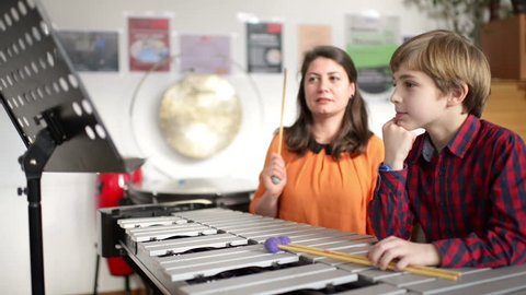 Kid studying percussion instrument vibraphone, teacher next to him