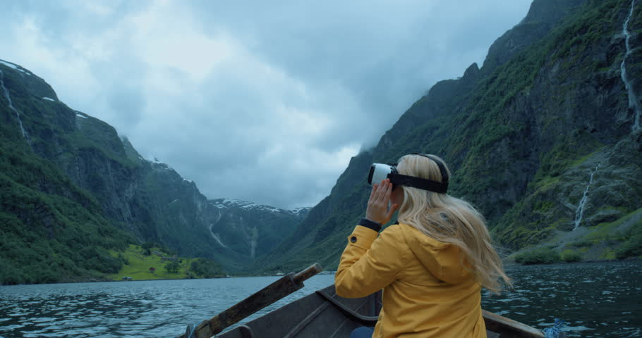 Brave woman traveler on row boat in Fjord Norway wearing virtual reality headset enjoying outdoor travel experience wearing yellow jacket  watching 360 video imagination concept