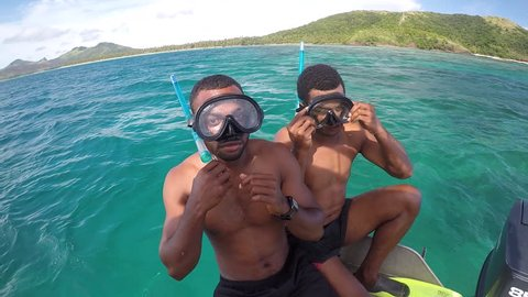 NADI, FIJI - DEC 20 2017:Indigenous Fijian men getting ready to snorkel in the Yasawa Islands of Fiji with Tourist.Fiji's annual Visitor Arrival number reached a new high of 792,320 in 2016.
