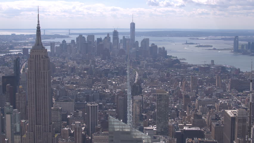 AERIAL CLOSE UP: Flying above the 6th avenue in sunny midtown Manhattan past the Empire state building and condominium apartment buildings towards downtown skyscrapers in New York City | Shutterstock HD Video #24378791