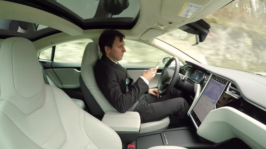 CLOSE UP: Young businessman texting writing messages on mobile phone while sitting behind self-driving steering wheel in autonomous autopilot driverless electric car traveling along countryside road #24380111