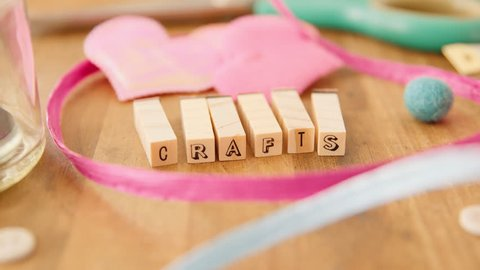 "Moving right to left along a table strewn with pretty coloured craft supplies and coming to rest on the word ""CRAFTS"" spelled out with wooden blocks."
