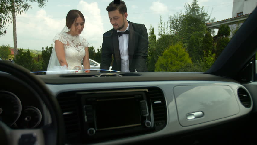 Bride and groom outdoor romantic scene. Looking at a map, next to a car. Setting the next travel destination. | Shutterstock HD Video #24382781