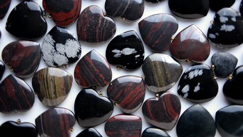 Snowflake obsidian red and iron tiger eye semiprecious stone hearts are rotating on white background top view