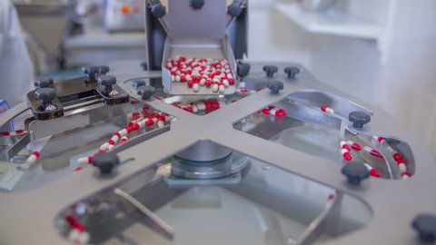Red-and-white pills are slowly coming out of a big box on a conveyor belt and theny will be sorted out into smaller cups.