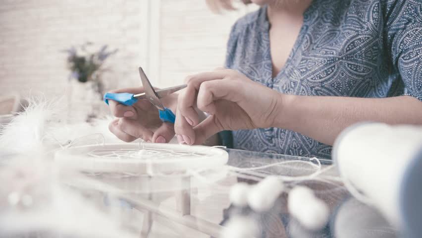 handmade dreamcatcher with bright feathers. Master makes new Dreamcatcher in art studio. Craftswoman shows Dreamcatcher.Process: The girl makes Dreamcatcher - Hobbies Crafts.