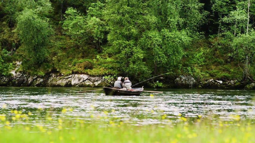 Handheld shot of senior men rowing boat while fishing on Nordic river   Shutterstock HD Video #24427121