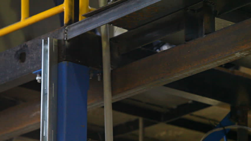 video shows metal construction installation process. This close-up shows metal cutting with small hand grinder with sparks flying down and metal is being cut. Video is taken indoors at factory site.