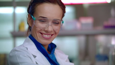 Woman scientist smiling. Happy scientist portrait in safety glasses. Scientist face. Female lab scientist smile. Closeup of lab woman happy face. Lab woman smiling