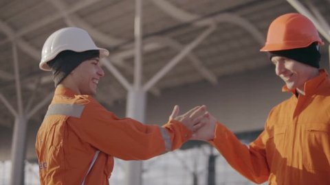 Two construction workers high five. They look very happy. New constructed building with columns at the background