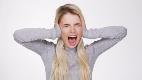Screaming blonde woman in sweater covering her ears with closed eyes
