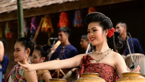 December 3, 2016, Nakhon Ratchasima. Isan women wearing traditional clothes dance to local music, with musicians playing in the background. Travel and culture concept.