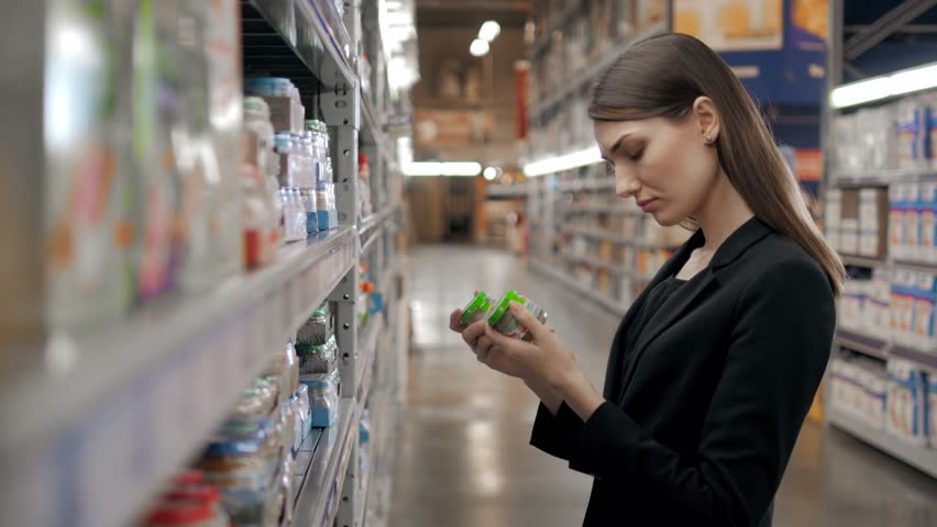 Happy female shopper searching for baby food in supermarket, yong mother mom in shop