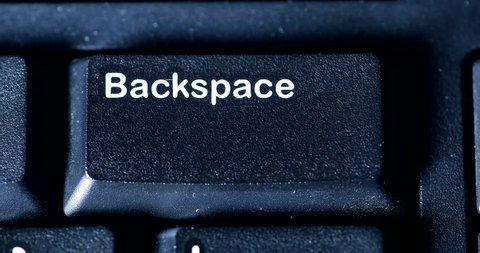 Human finger pressing a Backspace key on the computer keyboard