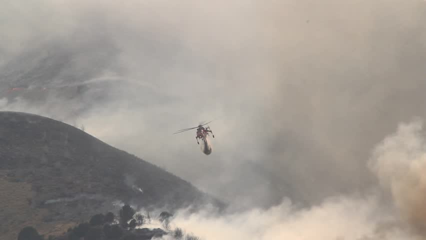A helicopter battles a gigantic wildfire on a dry mountainside, dropping hundreds of gallons of water on the flames. #2450501