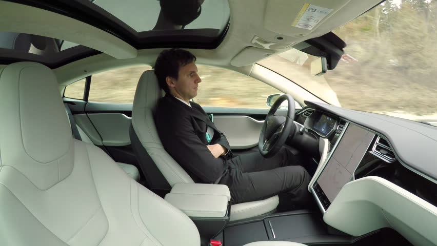 CLOSE UP: Relaxed businessman enjoying comfortable ride to work in autonomous self-driving autopilot driverless all-electric car on the highway through mountain forest on beautiful autumn morning | Shutterstock HD Video #24508481