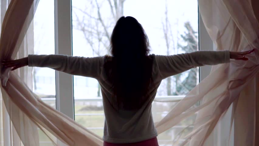 Young woman in sleeping costume opening the curtains in the morning at home