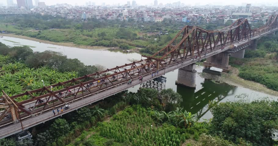 The famous Long Bien Bridge across the Red River connects the districts, Hoan Kiem and Long Bien of the capital Hanoi, Vietnam. Daily Millions of Motorcycles pass over this historic cantilever bridge.