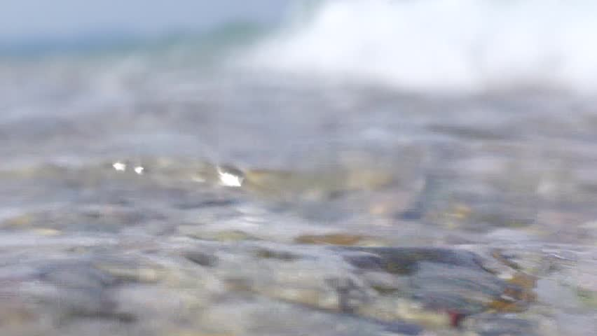 SLOW MOTION: Slow motion footage of sea waves forming at the shore and splashing over the camera which is pointed sideways.