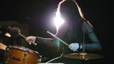 Girl rock musician - female drummer performing, slow-motion