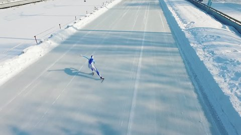 Speed ice skater skating on outdoor race HD video. Flying over professional athlete training for winter olympic.