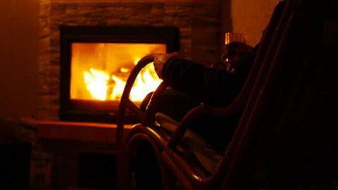 Man Sitting by the Fireplace in a Rocking Chair and with Glass of Wine in His Hand in the Dark Room