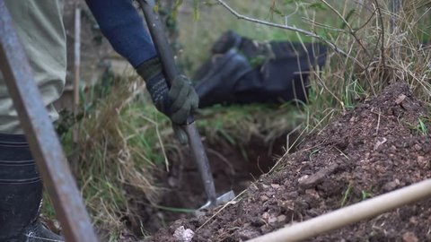 Murder dead body. Criminal digging a hole in the ground with a spade to bury and hide a corpse. Crime, violence, murder case with two people. Hiding the evidence. Homicide cover up outside.