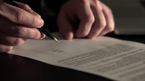 Close up shot of hands of the man who leaves his initials on the agreement. Senior signs a black pen on the contract, which he received in a large insurance company. Signature is fake.