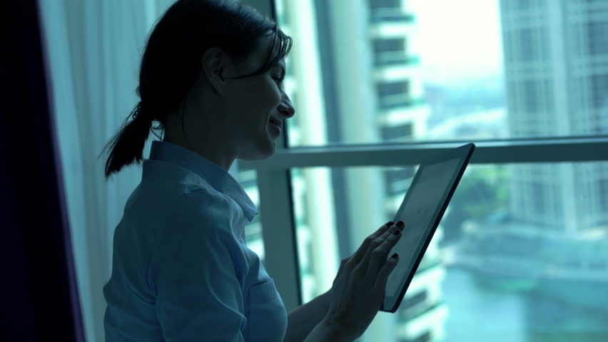 Young businesswoman browsing Internet on tablet by window at home  | Shutterstock HD Video #24596684