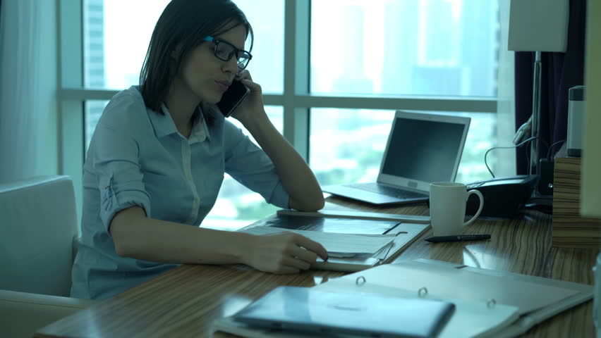 Angry businesswoman with documents talking on cellphone in office   | Shutterstock HD Video #24601799