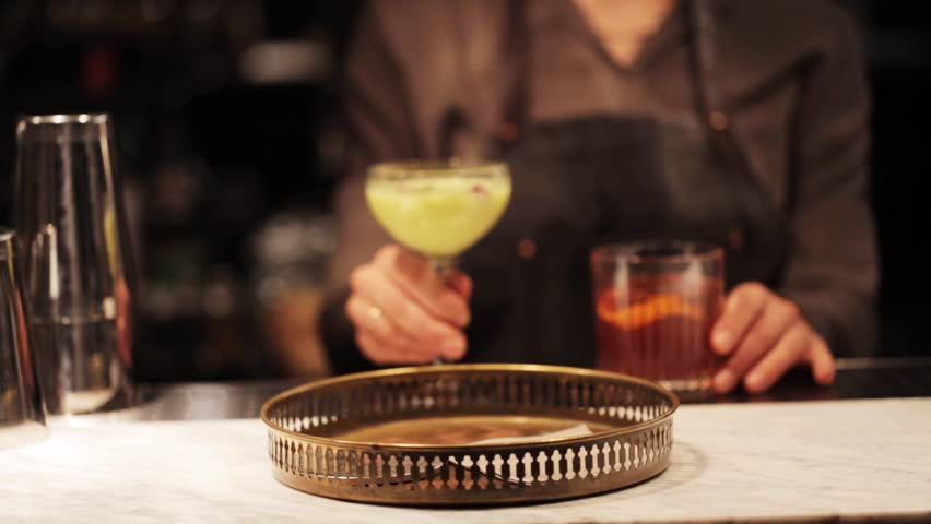 alcohol drinks, people and luxury concept - barmaid putting glasses of cocktails to tray at bar