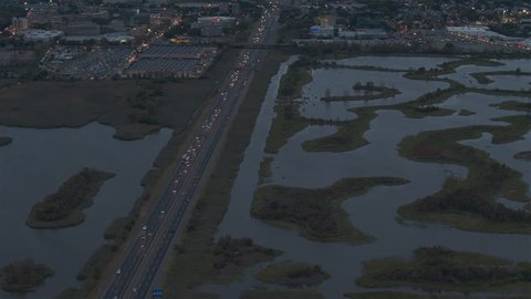 AERIAL HELI SHOT: Flying above turnpike highway leading through New Jersey swamp land towards the seaport after the sunset. Meandering river in heavily industrialized commercial zone of Newark Bay
