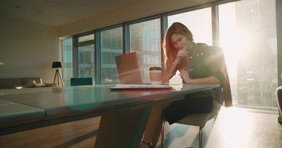 Young business woman sitting at a desk in a modern office in a skyscraper works, sun glare, steadicam shot | Shutterstock HD Video #24630911