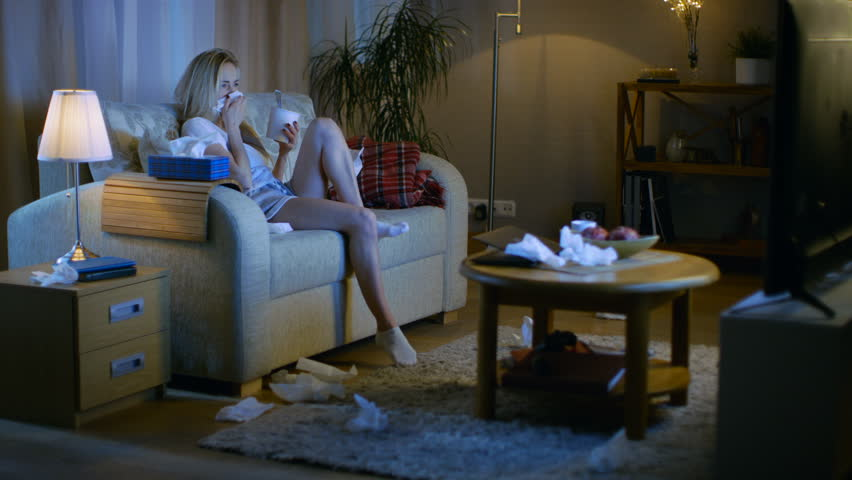 In the Evening Heartbroken Girl Sitting on a Sofa, Crying, Using Tissues, Eating Ice Cream and Watching TV. Her Room is in Mess. Shot on RED EPIC-W 8K Helium Cinema Camera.