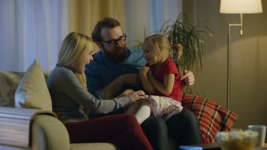 In the Evening Family Spends Time Together Sitting on a Couch in a Living Room. Little Girl Sits on Her Father's Laps and Parents Tickle Her. Shot on RED EPIC-W 8K Helium Cinema Camera.