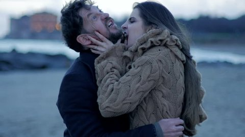Hungry beautiful female vampire attacking man trying to bite him on the beach at sunrise