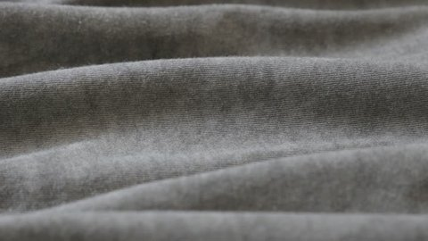 Close-up of dark grey smoked color fine t-shirt fabric 2160p 30fps UltraHD tilting footage - Silky gray modern clothing sample slow tilt 4K 3840X2160 UHD video