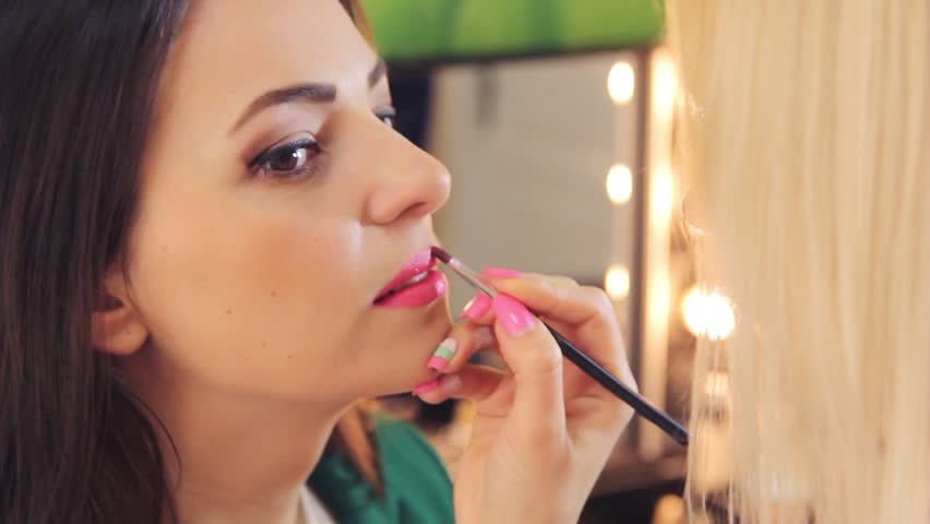 Beautiful girl put the makeup on the face | Shutterstock HD Video #24677741